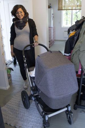 Emilia Jansson står i hallen och håller i en barnvagn.