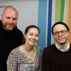 Olli Helenius, Essi Luttinen ja Veli Kauppinen seisovat Radio Suomen tunnuksen edessä