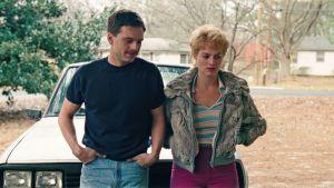 Jeff och Tonya står bredvid varandra lutade mot motorhuven på den gemensamma bilen.