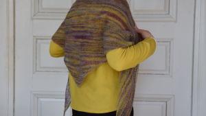 Stickad sjal över axlarna på en person