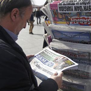 En man står och läser Zaman utanför en tidningskiosk i Istanbul på söndagen