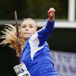 Blåklädde spjutkastaren Elina Kinnunen siktar spjutet mot skyn.