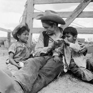 Jättiläinen-elokuvan kuvaukset Texasissa 1955.  James Dean tauolla sekä paikalliset lapset Roberto Marquez (vas.), Jose Luis Vasquez (oik.). Kuva tv-dokumentista Jättiläisen lapset.
