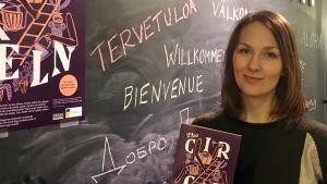Lisa Tobiasson framför en griffeltavla där det står välkommen på olika språk.
