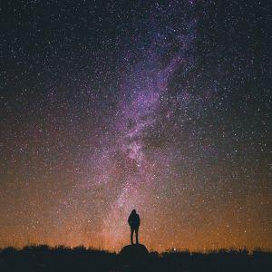 miehen siluetti katsoo Linnunrataa yötaivaalla
