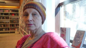 Minna Metzler i bibliotek. Bokhyllor och böcker i bakgrunden.