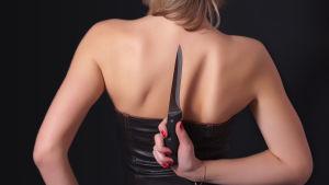 Kvinna döljer kniv bakom ryggen