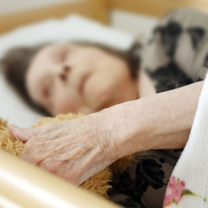 En ädlre kvinna ligger i en säng.