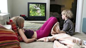 Två små barn sitter på sängen och tittar på barnprogram i tv.