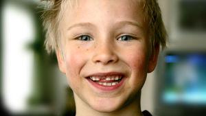 glad pojke visar framtänderna