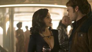 Qi'ra (Emilia Clarke) och Han Solo (Alden Ehrenreich) står och ser på varandra i en bar.