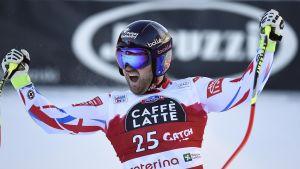 Alpinisten David Poisson jublar med utsträckta händer.