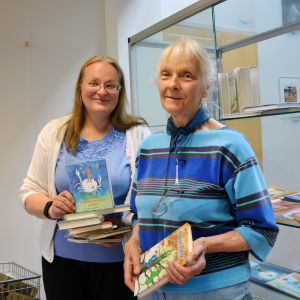 """Irmelin Sandman-Lilius och Suzanne """"Muddle"""" Lilius står med böcker i händerna i Hangö bibliotek."""