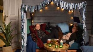 Vardagsrum med en tyghimmel ovanför soffan och två glada kvinnor i soffan.