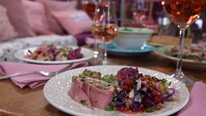Portion med buffemat och rosevin på ett bord.
