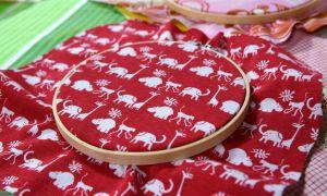 Syring med ett återvunnet rött tyg med mönster av små vita elefeanter och giraffer.