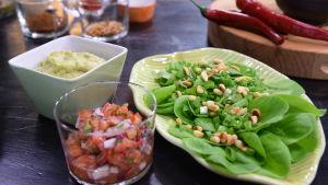 Tomatsalsa, guacamole med grönsallad på olika fat i ett kök.