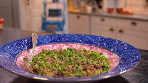 Bönsalsa av bondbönor och kryddor på en tallrik i ett kök.
