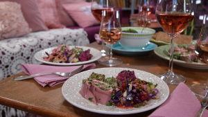 Portioner med buffémat och rosevin på ett bord.