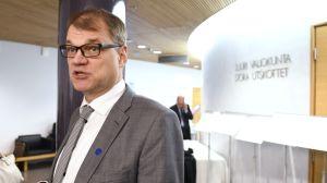 Statsminister Juha Sipilä i grå kostym fotograferad i riksdagen.