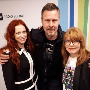 Jonsu, Antti Paavilainen ja Susanna Vainiola seisovat Radio Suomen tunnuksen edessä