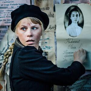 Iita (näyttelijä Milla-Mari Pylkkänen) on tehnyt etsintäkuulutuksen ystävästään Oliviasta.