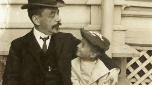 Man i hatt o mustach och pojke ser på varandra. Gammal bild