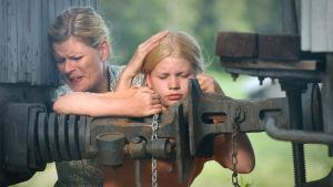 Marjatta Hovi (Maija Junno) ja tyttärensä Ella (Milja Siljamäki) suojautuvat pommilta (2003).