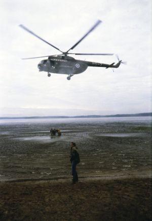 Helikopterin avulla tehdään aaltoja. Rannalla Ohjaaja Kalle Holmberg ja kuvausryhmä kuvaamassa järvessä.