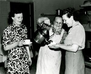 Tre kvinnor på rad, den mittersta häller upp kaffe ur en enorm kopparpanna.