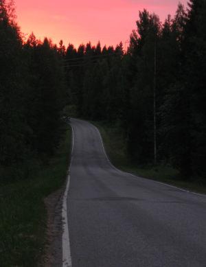 aurinko laskee, tie kiemurtelee metsässä
