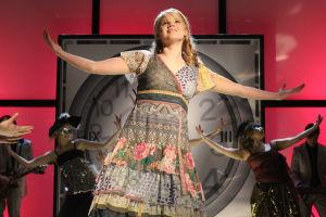 Vilma lavalla pitkä mekko päällään. Taustalla tanssijoita. Punainen tausta. Vilmalla kädet levitettynä.