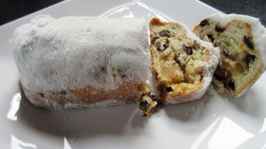 Sokerikuorrutettu Stollen-leivonnainen ja kaksi viipaletta leikattuna valkoisella tarjoilulautasella.