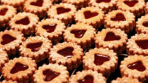 Kuvan täydeltä kerrospikkuleipiä, joissa päällä sydämenmuotoinen aukko ja sen keskellä punaista marmeladia.