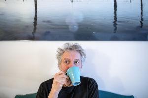 Jaakko Heikkilä istuu sohvalla ja juo kahvia.