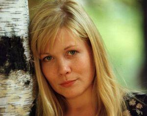 Kotikadun Laura Mäkimaa eli näyttelija Pirjo Moilanen nojaa koivuun ja katsoo kameraan