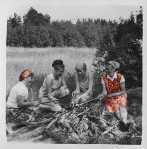 Vanha kuva, jossa on naisia nuotiolla.
