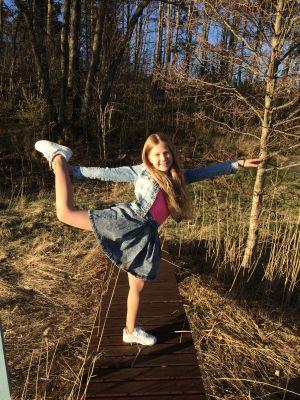 Elmina Arvidsson står på ett ben på en brygga.