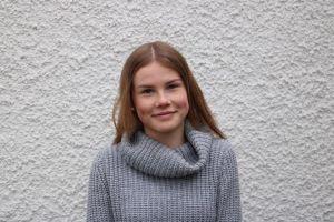 Emma Heiniö framför en stenvägg.