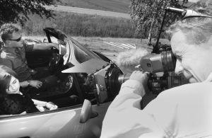 """Yleisradion televisio-ohjelma komediasarja (draamasarja) """"Rakastuin mä luuseriin"""". Ohjelman kuvaukset. Kuvaussunnittelija Harri Halonen työssä kuvaamassa. Autossa näyttelijät Panu Mikkola (roolinimi Make) ja Hanna Juvonen (roolinimi Outi). Työkuva. Yleisr"""