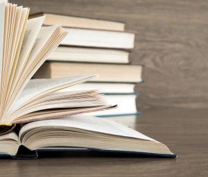 Två högar med böcker, i den främre högen är böckerna öppna.