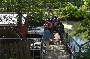 Ihmisiä pienen joen yli kulkevalla kävelysillalla katsomassa virtaavaa vettä ja vanhaa myllynratasta.