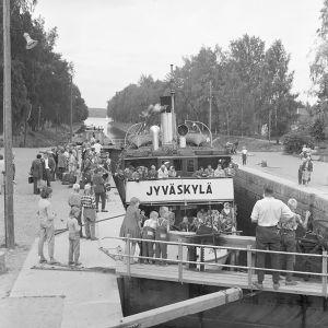 Mustavalkoinen kuva: Höyrylaiva S/S Jyväskylä Vääksyn kanavan suluilla ihmisten saartamana.