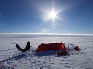Ett orange tält. Runt omkring finns bara is och snö. Solen lyser.