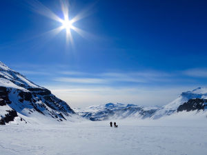 Två personer som skidar. Runt omkring finns berg och snö. Himlen är blå och solen skiner.