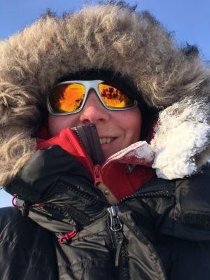 Kvinna med solglasögon och en stor jacka med pälskantad huva.