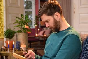 En man tittar på sin telefon med krokig nacke.