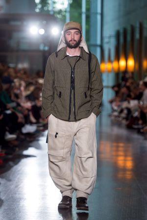 En man med beige byxor och en grön jacka. Han är modell på en modeshow.