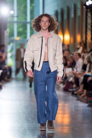 En manlig modell som går på en catwalk. Han är klädd i blåa byxor och en beige jacka.