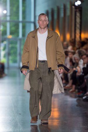 En manlig modell som går på en catwalk. Han är klädd i gråbruna byxor, en vit t-skjorta och en beige jacka.